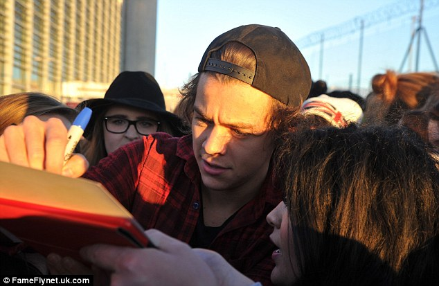 Harry Styles signs an autograph for a fan